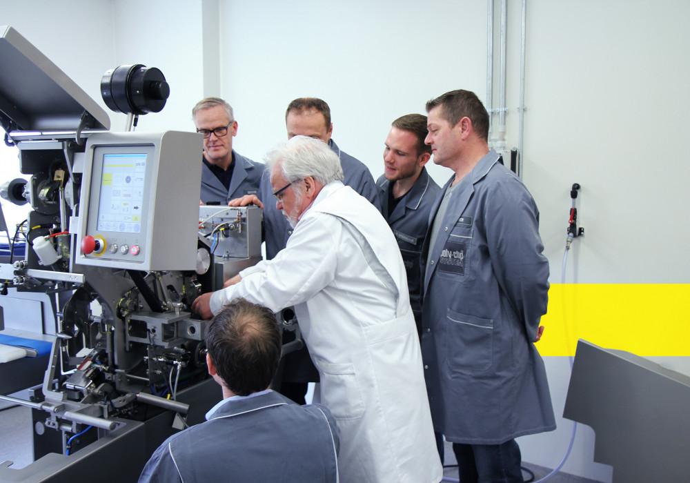 Employees around a machine